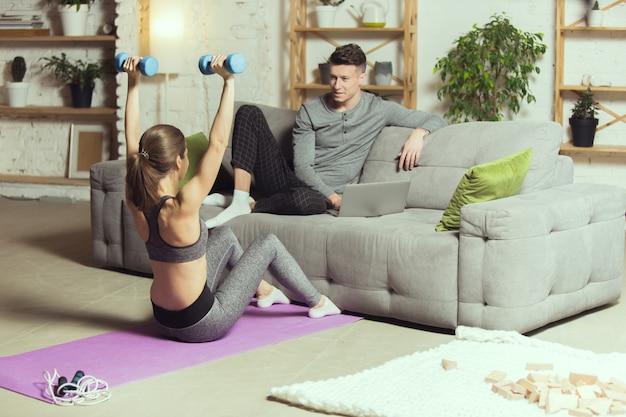 Mulher faz exercício em casa enquanto