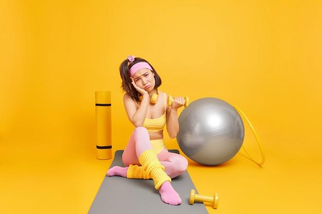 Mulher faz exercícios aeróbicos com halteres e uma bola de fitness vestida com roupas esportivas e senta-se em poses karemat de corpo inteiro