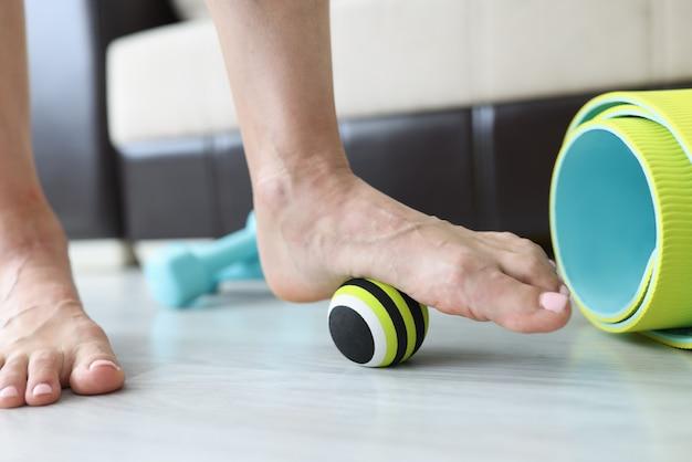 Mulher faz exercícios com bola para corrigir defeitos nos pés e pés chatos