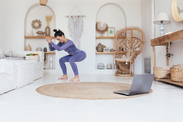 Mulher faz exercícios em casa e faz agachamento.