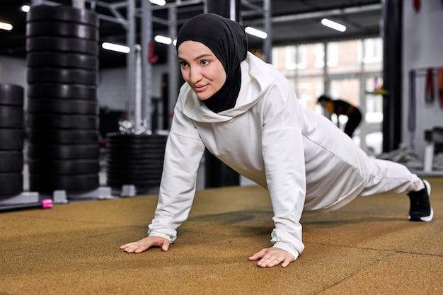 Mulher faz flexões. forte e em forma, atlética, muçulmana, exercitando-se sozinha em uma academia moderna. treino de treino, conceito de esporte