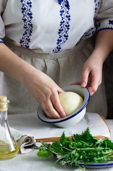 Mulher faz focaccia de massa de levedura com várias ervas. estilo rústico.