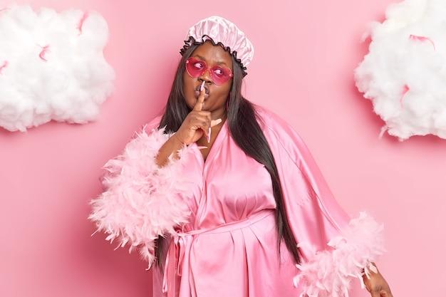 Mulher faz gesto de silene conta segredo mostra sinal de shh usa óculos escuros, roupão de seda e touca de banho posa em rosa