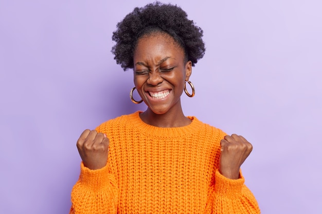 Mulher faz gesto de sim parece que o vencedor sorri amplamente comemora a vitória fica animado mantém os olhos fechados usa um suéter laranja casual tricotado isolado no roxo