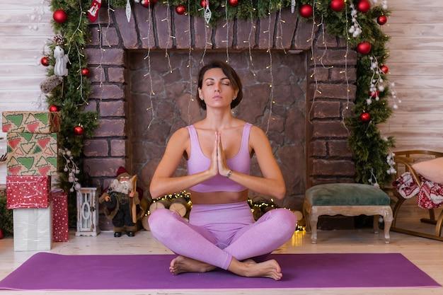 Mulher faz ioga em casa, plano de fundo de natal de ano novo.