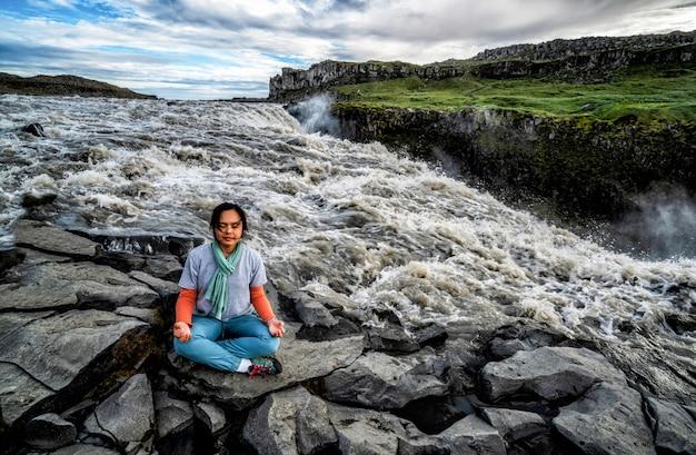 Mulher faz ioga na queda de dettifoss na islândia.