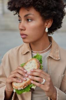 Mulher faz lanche na rua segura sanduíche delicioso come comida saborosa fast food olha de lado pensativamente vestida com roupas da moda posa do lado de fora