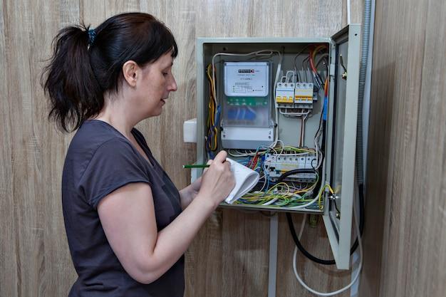 Mulher faz leituras de medidores de eletricidade, perto do painel elétrico do lado de dentro.