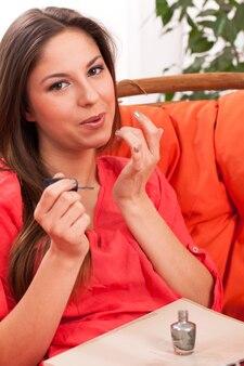 Mulher faz manicure em casa