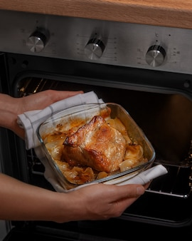 Mulher faz o ensopado e tira do forno. preparação de comida caseira. dieta protéica, dieta ceto