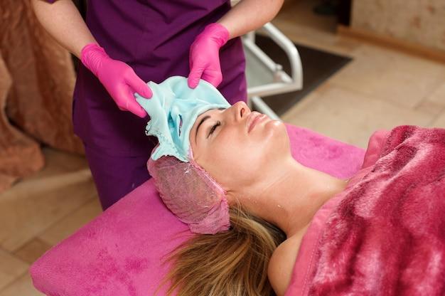 Mulher faz o procedimento no salão de beleza. máscara de alginato, limpeza ultrassônica. cuidados com a pele facial. procedimentos de cosmetologia sem cirurgia.