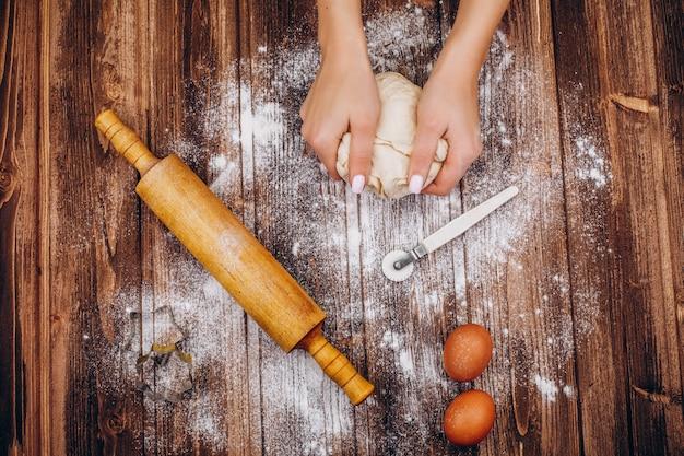 Mulher faz pastelaria de natal na massa na mesa de madeira