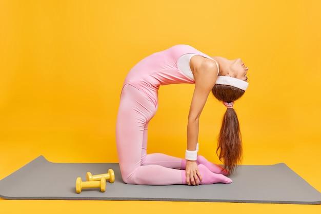 Mulher faz pilates no tapete de fitness tem corpo esguio perfeito inclinado para trás usa bandana e exercícios de roupa ativa com halteres isolados em amarelo