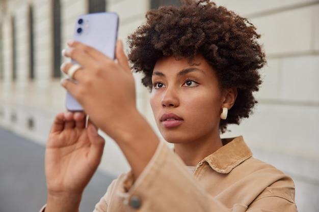 Mulher faz selfie na câmera frontal de poses de smartphone para tirar foto de si mesma do lado de fora enquanto faz uma excursão na cidade, usa roupas elegantes e tem tempo livre