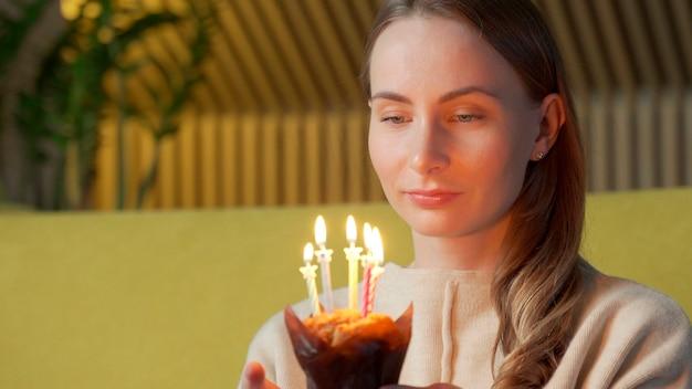 Mulher faz um pedido, apaga as velas de um bolo de aniversário e ri