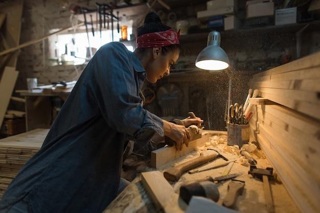 Mulher faz um trabalho de madeira na oficina. artesão em processo de trabalho