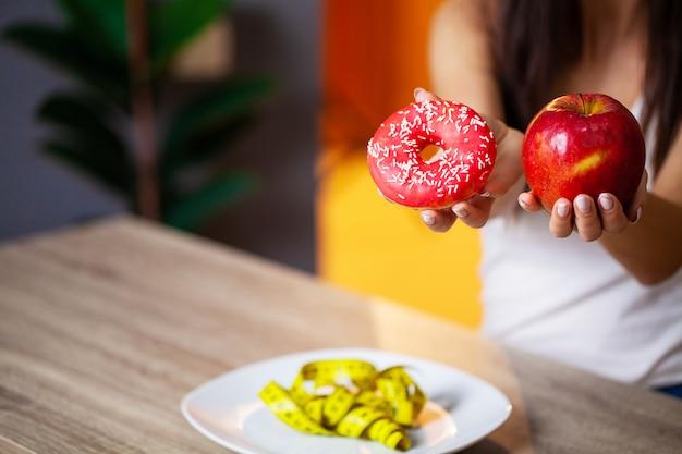 Mulher faz uma escolha entre alimentos prejudiciais e saudáveis