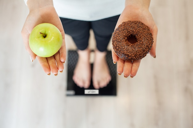 Mulher faz uma escolha entre alimentos saudáveis e prejudiciais