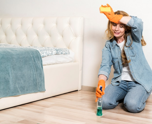 Mulher faz uma pausa na limpeza do chão