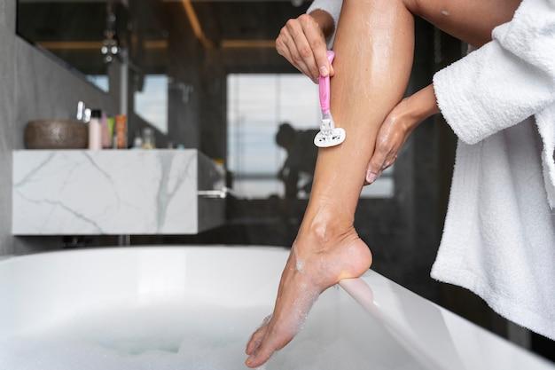 Mulher fazendo a barba antes de tomar banho