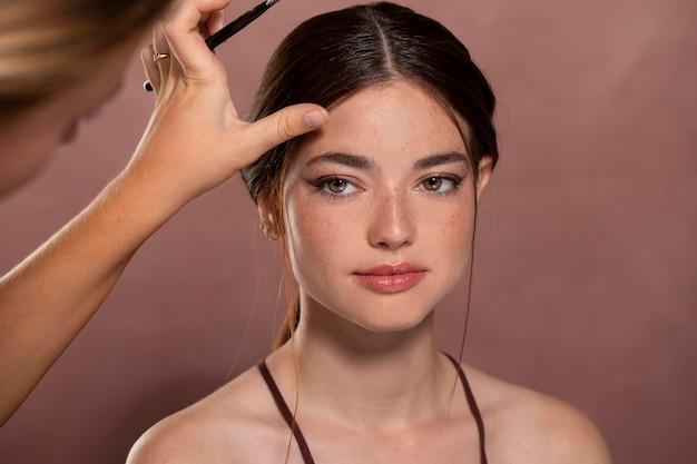 Mulher fazendo a maquiagem por um profissional