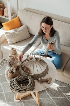 Mulher fazendo abajur artesanal com corda de juta