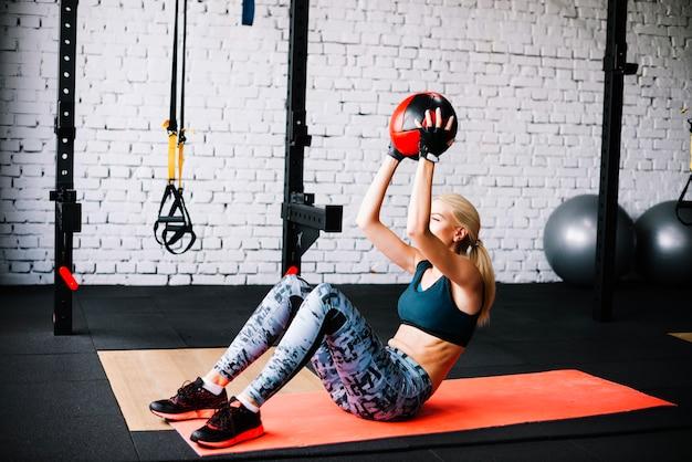 Mulher fazendo abas abdominais com bola