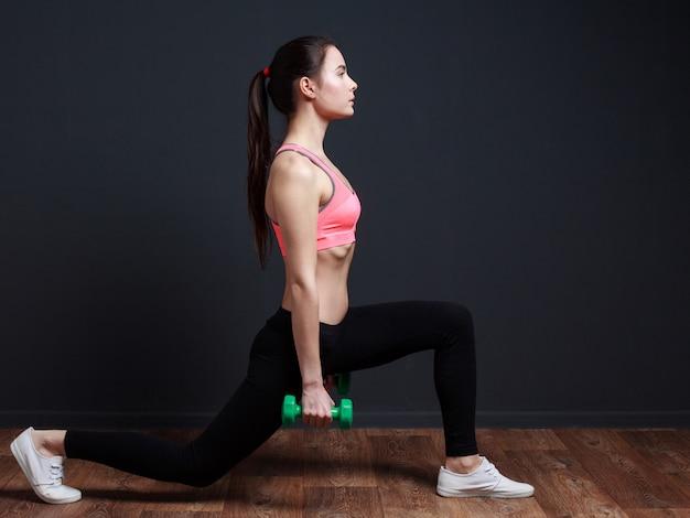 Mulher fazendo agachamento estocada frontal com peso