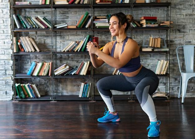 Mulher fazendo agachamento treino e sorrindo durante o treino de fitness em casa