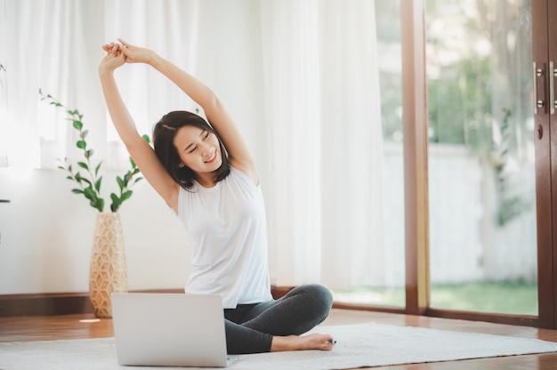 Mulher fazendo alongamento exercício de aquecimento na sala de estar em sua casa
