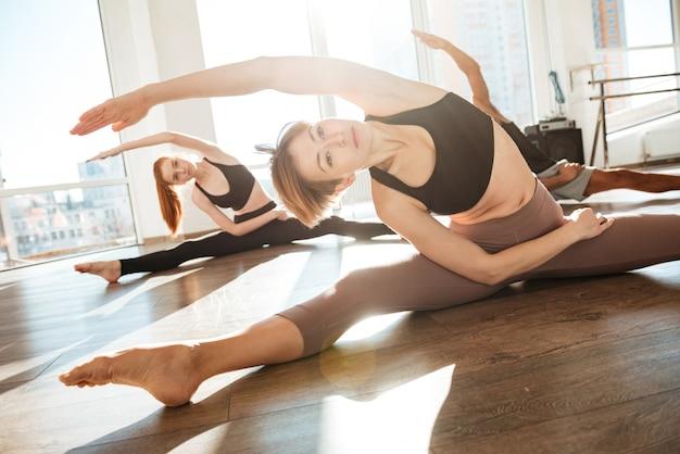Mulher fazendo alongamento exercícios em grupo no estúdio de yoga