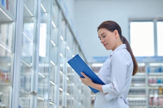 Mulher fazendo anotações perto de prateleiras de remédios na farmácia