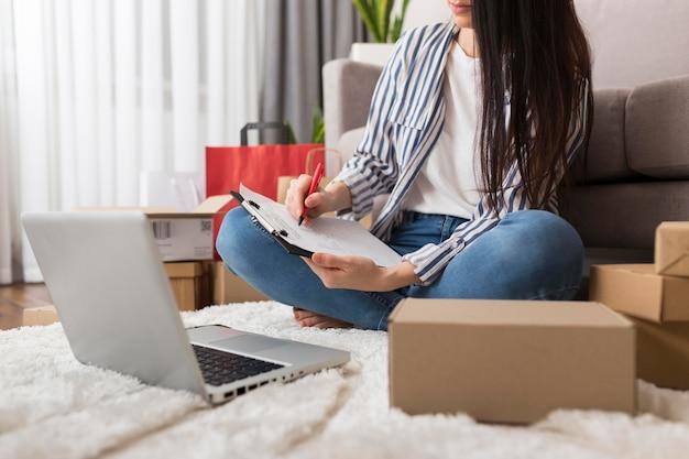 Mulher fazendo anotações sobre compras cibernéticas de segunda-feira