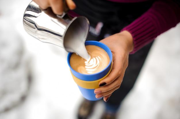 Mulher fazendo arte de café com leite na cafeteria