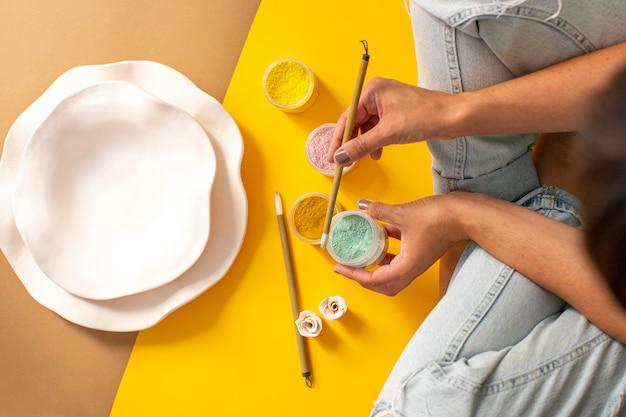 Mulher fazendo artesanato com pincéis e tintas em fundo de tons quentes