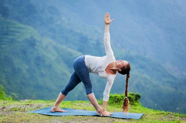 Mulher fazendo ashtanga vinyasa yoga asana parivrtta trikonasana