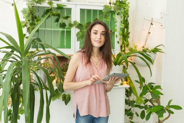 Mulher fazendo batota usando um laptop ou navegando na internet em uma sala com plantas verdes