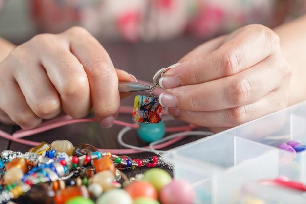 Mulher fazendo bijuteria de arte de artesanato em casa