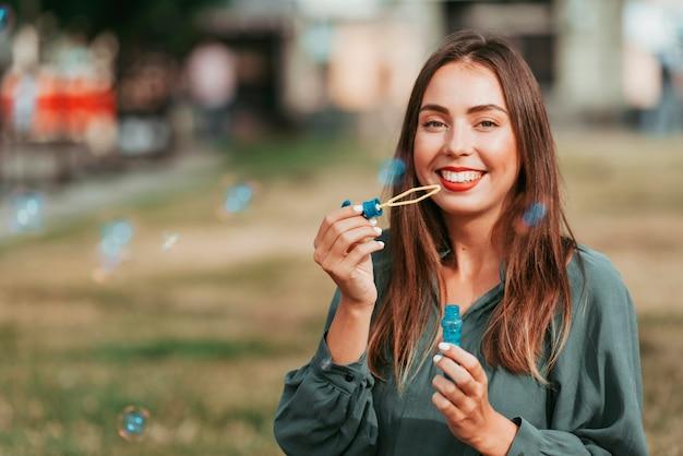 Mulher fazendo bolhas de sabão com espaço de cópia