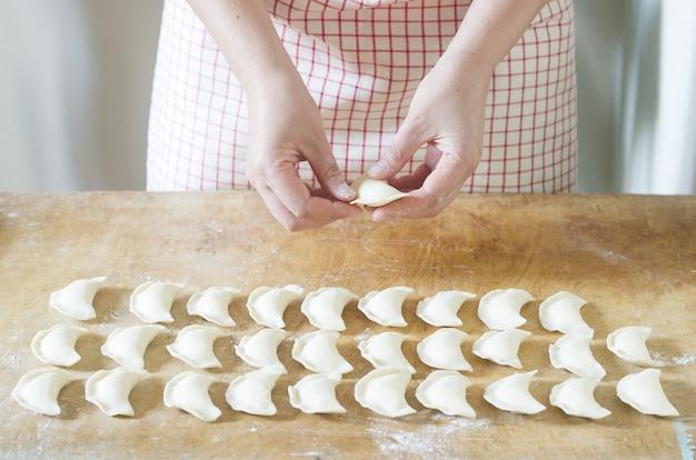 Mulher fazendo bolinhos de massa, vareniks. feito à mão.