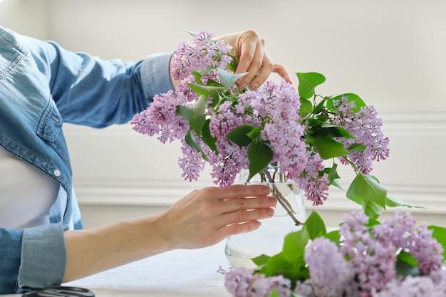 Mulher fazendo buquê de ramos lilás, close-up feminino organizando ramo de flores em vaso