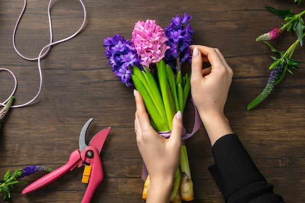 Mulher fazendo buquê moderno de flores diferentes na superfície de madeira