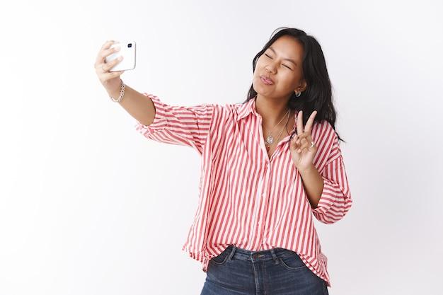 Mulher fazendo caretas como tendo selfie no smartphone. retrato de mulher asiática boba fofa brincalhona e despreocupada com blusa listrada, mostrando a língua e o símbolo da paz fazendo fotos sobre uma parede branca
