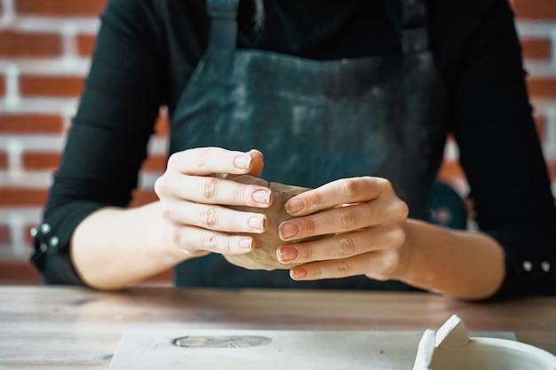 Mulher fazendo cerâmica, mãos closeup, turva, foco em oleiros, palmas das mãos com cerâmica