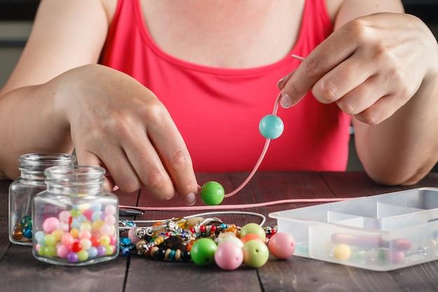 Mulher fazendo colar de miçangas coloridas