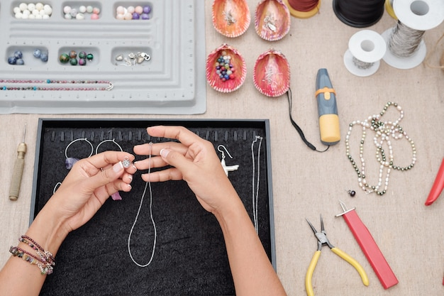 Mulher fazendo colar