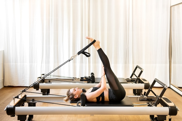 Mulher fazendo coluna curta pilates exercícios