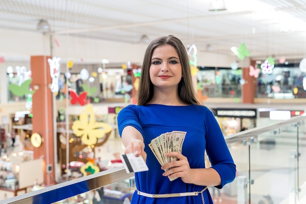 Mulher fazendo compras com dólares e cartão de crédito