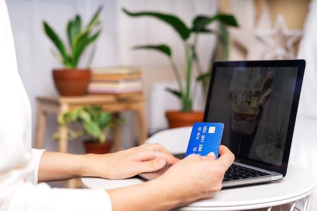 Mulher fazendo compras com laptop e cartão de crédito