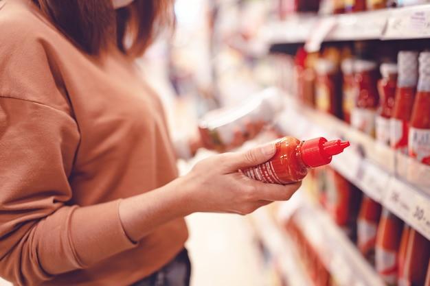 Mulher fazendo compras no supermercado e lendo informações sobre o produto